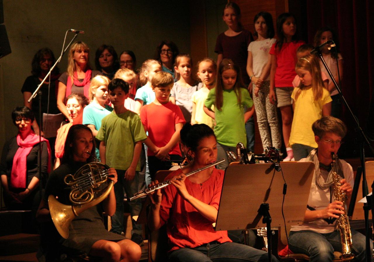 Musiker mit dem Kinderchor im Hintergrund